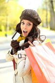 image of jaw drop  - Fashion trendy woman showing credit card and carrying shopping bags after buying in autumn - JPG
