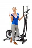 picture of elliptical  - Young woman uses elliptical cross trainer - JPG