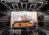stock photo of pastry chef  - Chef prepares pastries in the oven - JPG