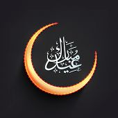 image of eid mubarak  - Golden crescent moon with arabic islamic calligraphy of text Eid Mubarak on black background - JPG