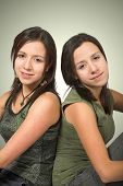 stock photo of sissi  - beautiful twin sisters in green over a green background - JPG