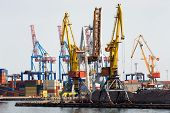 picture of loading dock  - Industrial cranes and cargo on a quay in a docks waiting to be loaded onto ships for transport to overseas destinations - JPG