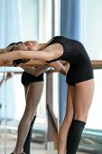 foto of ballet barre  - Young graceful ballet dancer stretching out at the barre in the studio - JPG