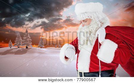 Festive santa claus checking time against snowy landscape with fir trees