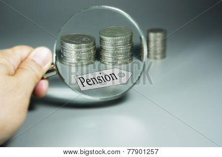 Magnifier, Pension Tag, And Stack Of Coins In The Backdround
