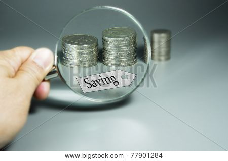 Magnifier, Saving Tag, And Stack Of Coins In The Backdround