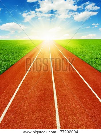 Running track in field with sky and clouds