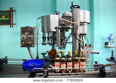 Bottles of rum on production line in distillery, in Vinales, Cuba