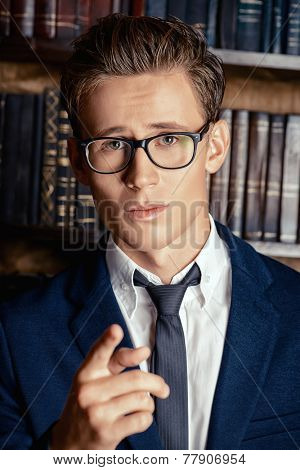 Close-up portrait of a respectable handsome man in his cabinet, library. Classic vintage style.