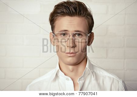 Portrait of a sad handsome young man in white shirt.