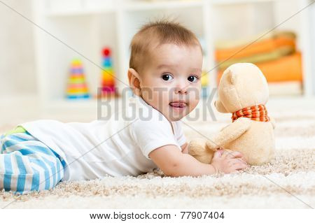 baby boy lying with plush toy