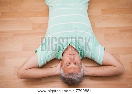 Mature man lying on floor at home in the living room