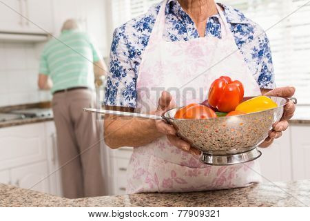 Senior woman showing colander of vegetables at home in the kitchen