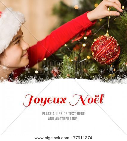 Festive little girl hanging a christmas decoration against joyeux noel