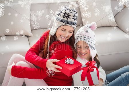 Mother and daughter exchanging gifts at christmas against snowflakes
