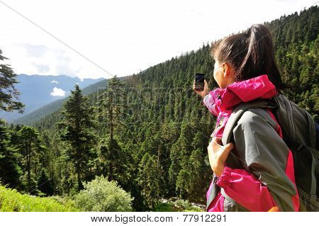 woman tourist taking photo with cell phone at mountain peak in tibet,china