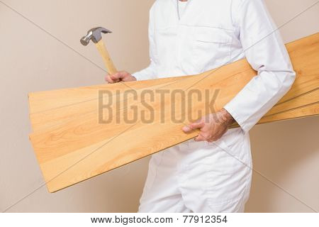 Carpenter holding planks and hammer in a new house