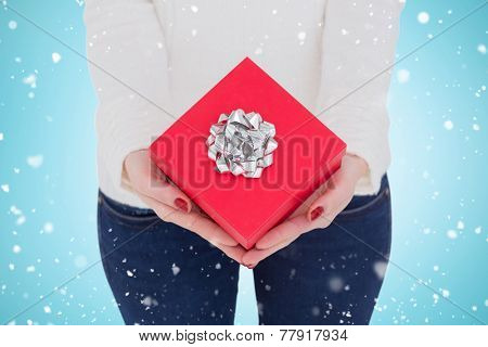 Woman with nail varnish holding red gift against blue vignette