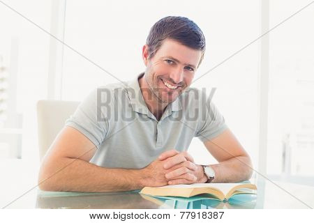 Casual businessman sitting at desk reading a book in his office