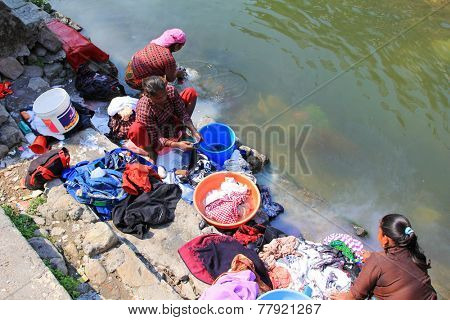 POKHARA, NEPAL - APRIL 15 : Nepalese women washing clothes along the river on 15 April 2014 in Pokhara city, Nepal.