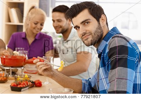 Young man having fondue party with friends, holding dipping stick, smiling, looking at camera.