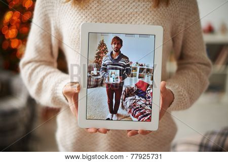 Young female showing image of her sweetheart in touchpad while he holding one with portrait of her