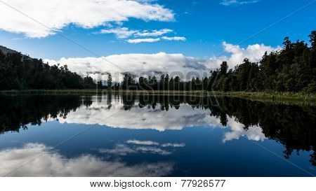 Lake Matheson reflecting the clouds with a small tip of Mount Cookpeeking through the layer of cloud