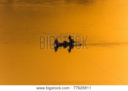 Two fishermen fishing on a lake in Sri Lanka while the setting sun illuminates their fishing grounds