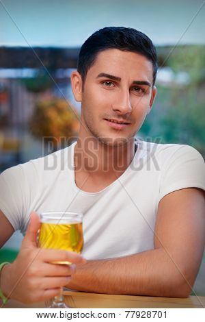 Young Man Holding a Glass in a Bar
