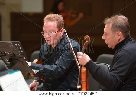 NOVOSIBIRSK, RUSSIA - DECEMBER 5, 2014: Moscow Soloists's second violins A. Dyrul (left) and M. Gurevich on the rehearsal during the festival Classics. The event joins concerts of World music stars