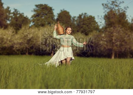 Girl With A Pitcher Is On The Field With Grass.