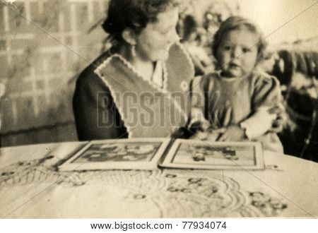 GERMANY, DECEMBER 25, 1938: Mother read a book with a little daughter