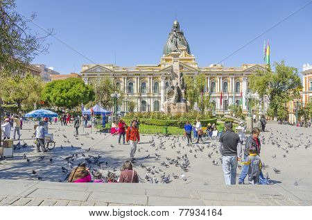 LA PAZ, BOLIVIA, MAY 8, 2014: People walk at Plaza Murillo (monument of Pedro Domingo Murillo and Government Palace of Bolivia in background)