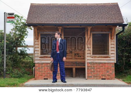 Businessman Standing At A Bus Stop In Pyjamas And Slippers
