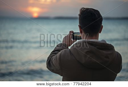 Man Takes Photographs Sunset Over The Sea