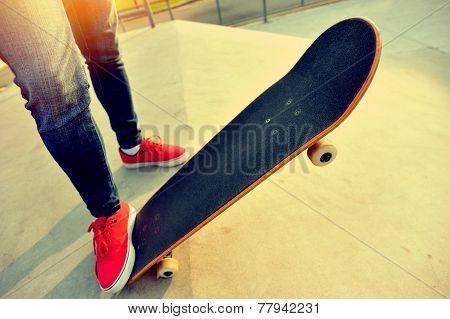 young woman legs skateboarding at skatepark