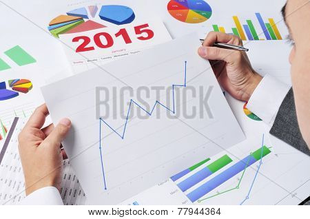 businessman in his office desk observing a chart with an upward trend, with a 2015 calendar in the background