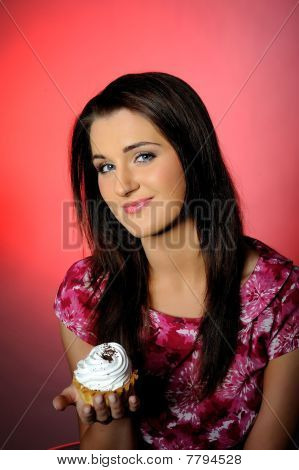 Young Beautiful Girl Eating Small Sweet Cake. Pink Background