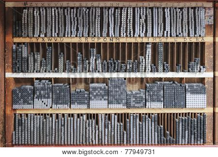 Printing press letter blocks in wooden shelf
