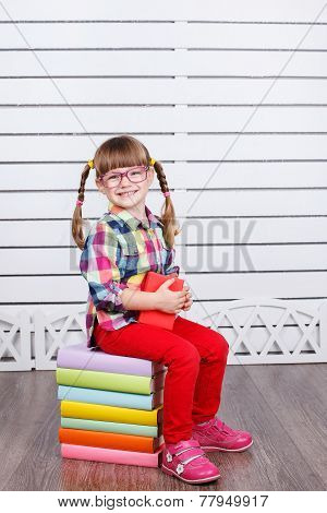 Little girl sitting on a stack of textbooks .
