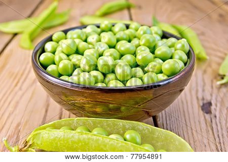 Green peas in brown bowl and pod on board