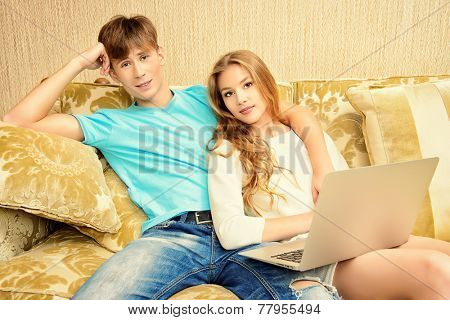 Happy young couple websurfing on internet with laptop. They sit in the cozy living room of their home.