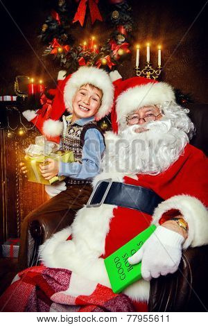 Santa Claus and laughing cute boy sitting in Christmas room with gifts. Christmas home decor.