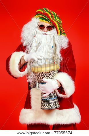 Casual Santa Claus hippie playing a drum over festive red background.