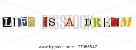 The phrase Life is a Dream formed with magazine letters on white background