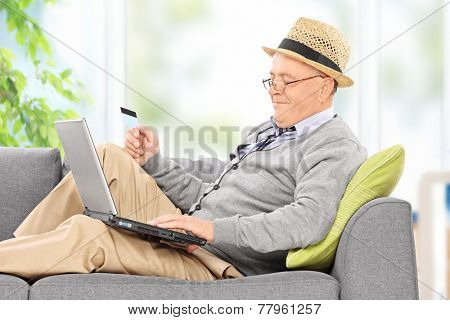 Senior working on laptop and holing credit card seated on a sofa at home