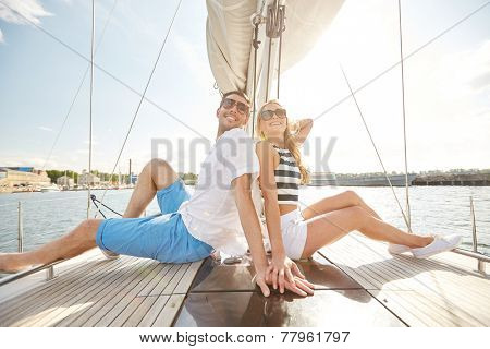 vacation, travel, sea, friendship and people concept - smiling couple sitting and talking on yacht deck