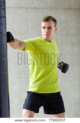 sport, box and people concept - young man in gloves boxing with punching bag in gym