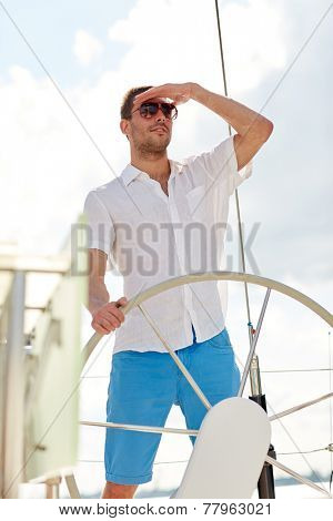 vacation, holidays, travel, sea and people concept - young man in sunglasses steering wheel and looking far away on yacht