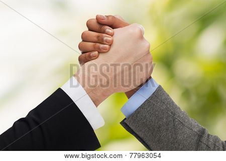 business, people and competition concept - close up of two people hands arm wrestling over green background